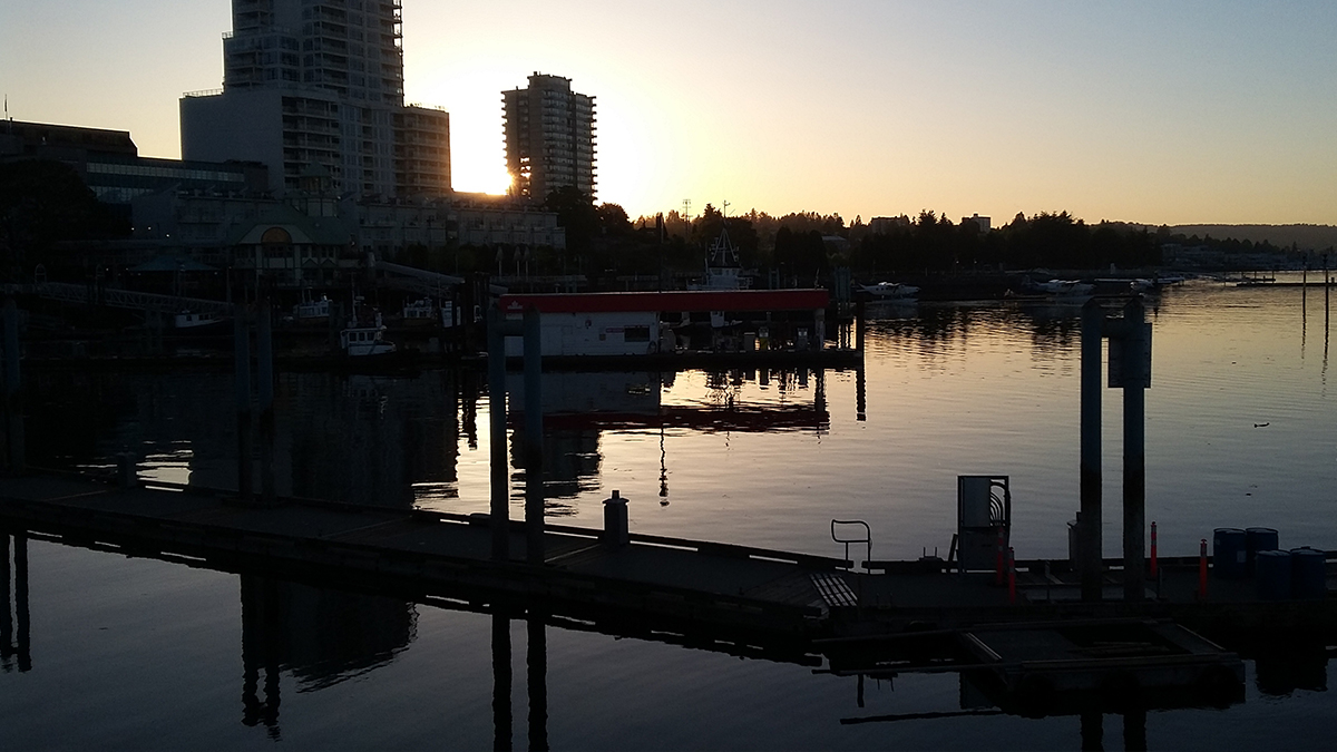 a dock area at a sunset point with the shadows of the building reflecting in the water
