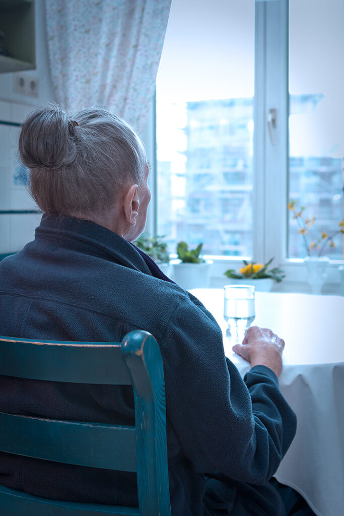 Old woman sitting alone at her kithchen table with a glass of water looking out of the window, blue filter effect, concept of old-age depression, loneliness