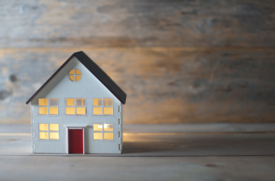 Miniature house over a wooden background for bc rent bank