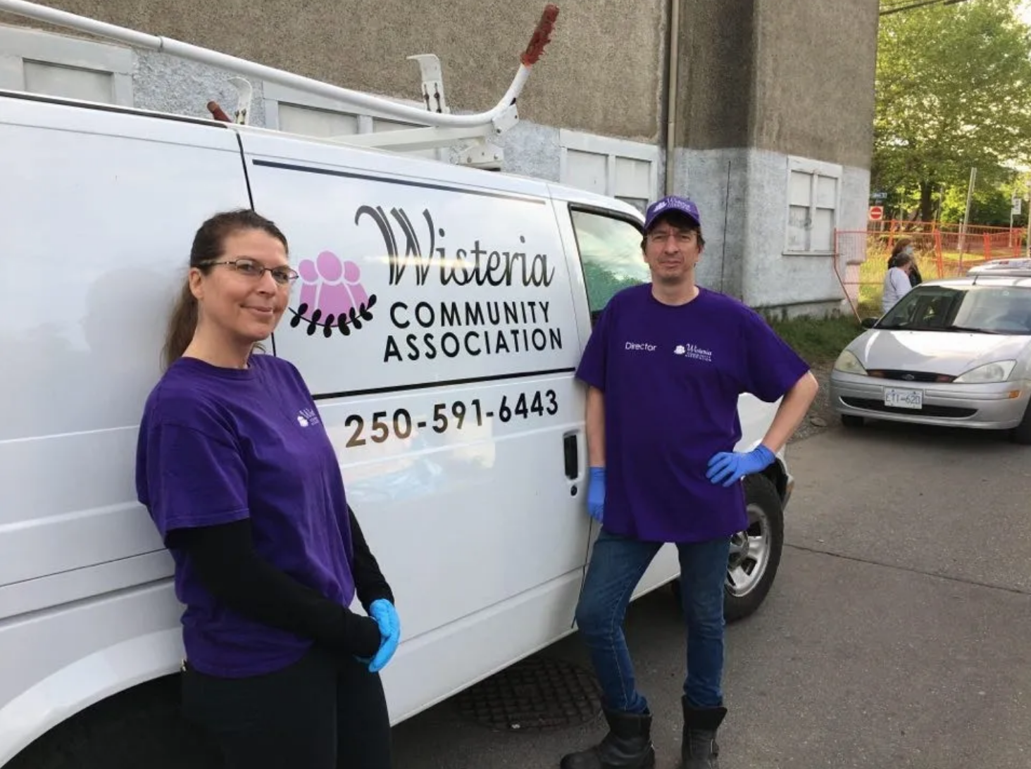 two people wearing purple shirts standing against a white truck