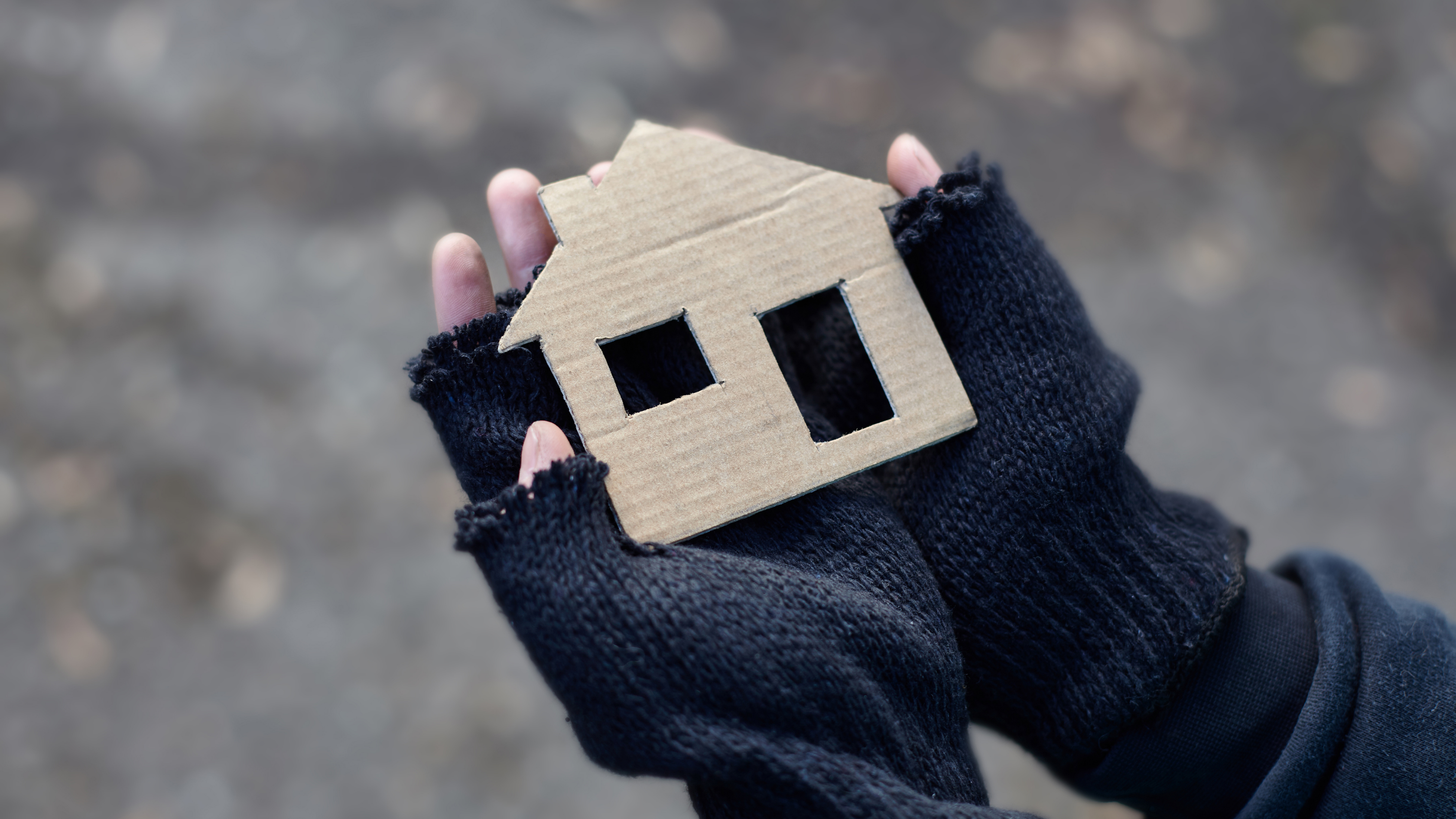 Hands holding a house to demonstrate people struggling with homelessness